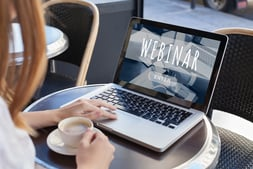 Woman holding a cup of coffee, looking at open laptop with webinar on the screen